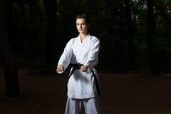 Femme dans le karaté blanc de formation au parc photographie stock libre de droits