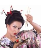 Femme dans le kimono japonais avec les baguettes et le petit pain de sushi Photos libres de droits