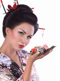 Femme dans le kimono japonais avec les baguettes et le petit pain de sushi Image libre de droits