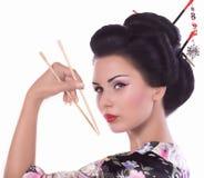 Femme dans le kimono japonais avec les baguettes et le petit pain de sushi Photographie stock libre de droits
