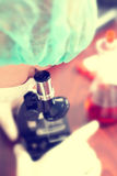 Femme dans le laboratoire de chimie avec le microscope Photos libres de droits