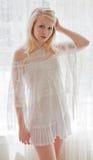 Femme dans le lacet blanc par les rideaux de dentelle blancs Image stock