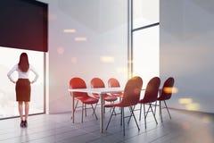 Femme dans le lieu de réunion blanc avec les chaises rouges images stock