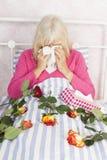 Femme dans le lit avec des roses et des tissus Photo stock