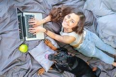 Femme dans le lit avec le grand chien Photos libres de droits