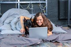 Femme dans le lit avec le grand chien Photographie stock