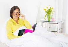 Femme dans le lit avec un livre Image libre de droits