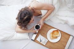 Femme dans le lit mangeant le petit déjeuner Photo libre de droits