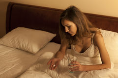 Femme dans le lit prenant des comprimés somnifères Image libre de droits