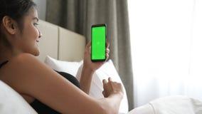Femme dans le lit utilisant le téléphone portable avec la clé verte de chroma d'écran banque de vidéos