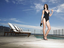 Femme dans le maillot de bain avec Champagne Bottle By Pool Photo libre de droits