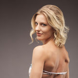 Femme dans le maillot de bain blanc de lingerie dans le studio Amincissez la fille blonde posant et souriant à l'appareil-photo Photo libre de droits