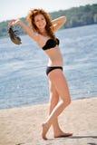 Femme dans le maillot de bain marchant le long du bord de la mer photographie stock