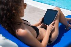 Femme dans le maillot de bain tenant le comprimé numérique avec l'écran vide de l'espace de copie pour votre publicité Photos libres de droits