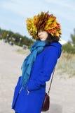 Femme dans le manteau avec des feuilles d'érable Photos stock