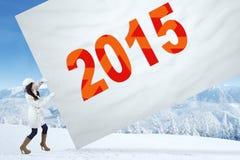 Femme dans le manteau d'hiver avec le numéro 2015 Photos stock