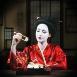 Femme dans le maquillage de geisha mangeant des sushi Image stock