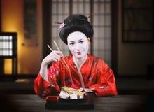 Femme dans le maquillage de geisha mangeant des sushi Image libre de droits
