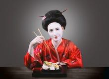 Femme dans le maquillage de geisha mangeant des sushi Photos stock