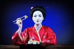 Femme dans le maquillage de geisha mangeant des sushi Photos libres de droits