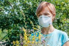 Femme dans le masque de protection tenant le bouquet des wildflowers et du tryi Images stock