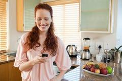 Femme dans le message textuel d'écriture de cuisine Photo stock
