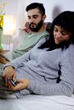 Femme dans le message textuel de dissimulation de lit de l'ami jaloux Images stock