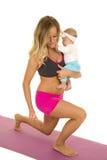 Femme dans le mouvement brusque de vêtement de forme physique tenant le bébé Image libre de droits