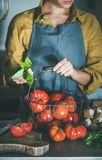 Femme dans le panier de participation de tablier avec des tomates d'héritage pour la cuisson photos stock