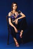 Femme dans le pantalon bleu plissé et le dessus floral se reposant sur la chaise Photographie stock