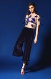 Femme dans le pantalon plissé bleu-foncé et le dessus transparent floral Photo stock