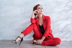 Femme dans le pantsuit rouge à la mode dans le studio photos libres de droits