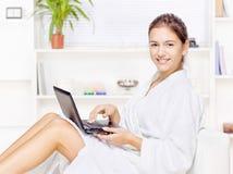 Femme dans le peignoir avec l'ordinateur Photographie stock libre de droits