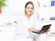 Femme dans le peignoir avec l'ordinateur Photo stock