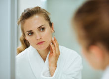 Femme dans le peignoir contrôlant son visage dans le miroir Photographie stock