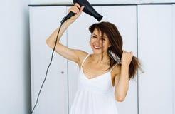 Femme dans le peignoir séchant ses cheveux avec le dessiccateur au-dessus du fond blanc photographie stock