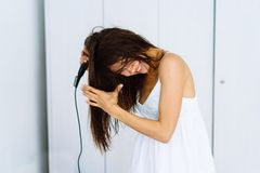 Femme dans le peignoir séchant ses cheveux avec le dessiccateur au-dessus du fond blanc image stock