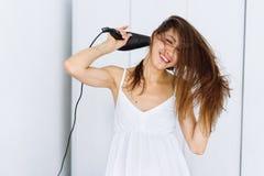 Femme dans le peignoir séchant ses cheveux avec le dessiccateur au-dessus du fond blanc photo stock