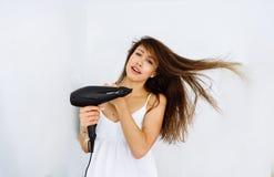 Femme dans le peignoir séchant ses cheveux avec le dessiccateur au-dessus du fond blanc photographie stock libre de droits