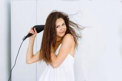 Femme dans le peignoir séchant ses cheveux avec le dessiccateur au-dessus du fond blanc images stock