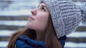 Femme dans le profil regardant au ciel d'hiver Jeune femme attirante avec le regard rêveur banque de vidéos