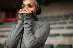 Femme dans le pull molletonné se tenant dans un stade écoutant la musique image stock