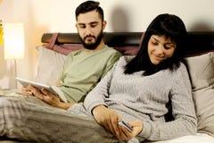 Femme dans le regard jaloux d'ami de message textuel de lit Photographie stock libre de droits