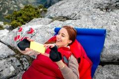 Femme dans le sac de couchage sur la montagne Photos stock