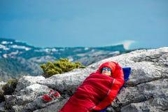 Femme dans le sac de couchage sur la montagne Image libre de droits