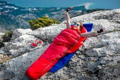 Femme dans le sac de couchage sur la montagne Photo libre de droits