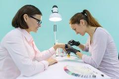 Femme dans le salon d'ongle recevant la manucure par le manucure, processus de manucure de plan rapproché Soin d'ongle et de main images stock