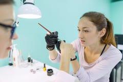 Femme dans le salon d'ongle recevant la manucure par le manucure, processus de manucure de plan rapproché Soin d'ongle et de main photographie stock libre de droits
