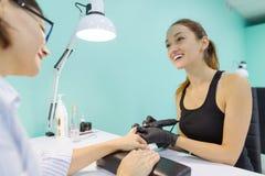 Femme dans le salon d'ongle recevant la manucure par le manucure, processus de manucure de plan rapproché Soin d'ongle et de main photos libres de droits
