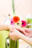 Femme dans le salon de clou recevant le massage de main Photographie stock libre de droits